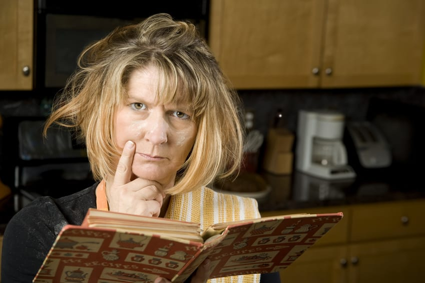 Woman consulting a cookbook